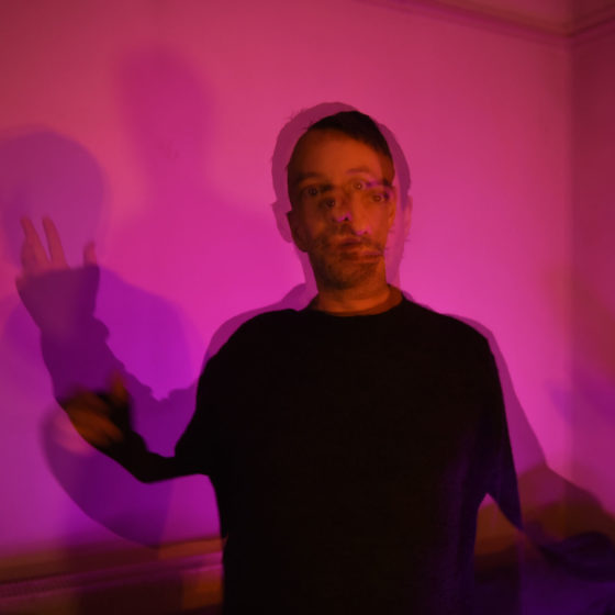 Ivan Smagghe standing in room with pink light